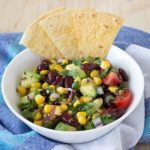 Wholesome and very healthy black bean, corn and avocado salad served with homemade tortilla chips is ideal for big family and friends gatherings. Seasoned with lime and cumin dressing, it's refreshing, delicious and flavorful, perfect spring and summer salad. Click to read more or PIN for later!
