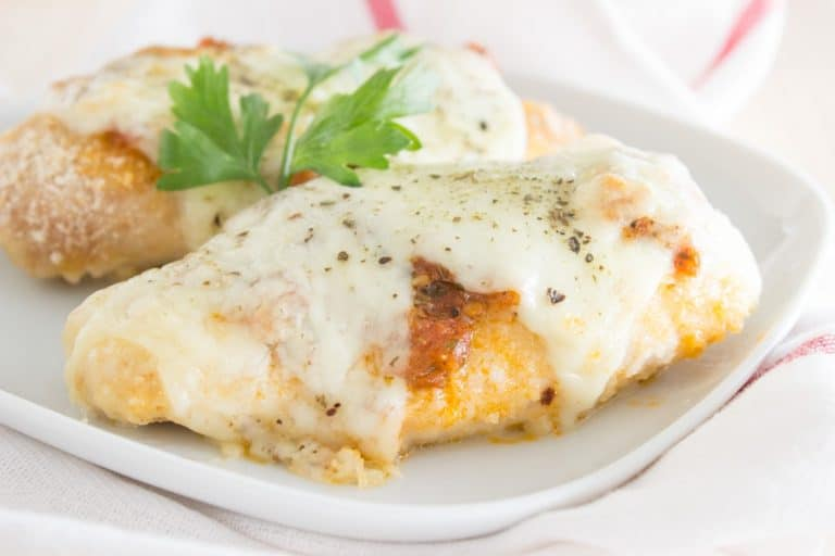Easy Chicken Parmesan baked in the oven with mozzarella cheese and homemade tomato sauce, seasoned with fragrant spices. This dish is made without added fat, which makes this meal super healthy and low-fat. Perfect weekday dinner your family will love. CLICK to read more or PIN for LATER!