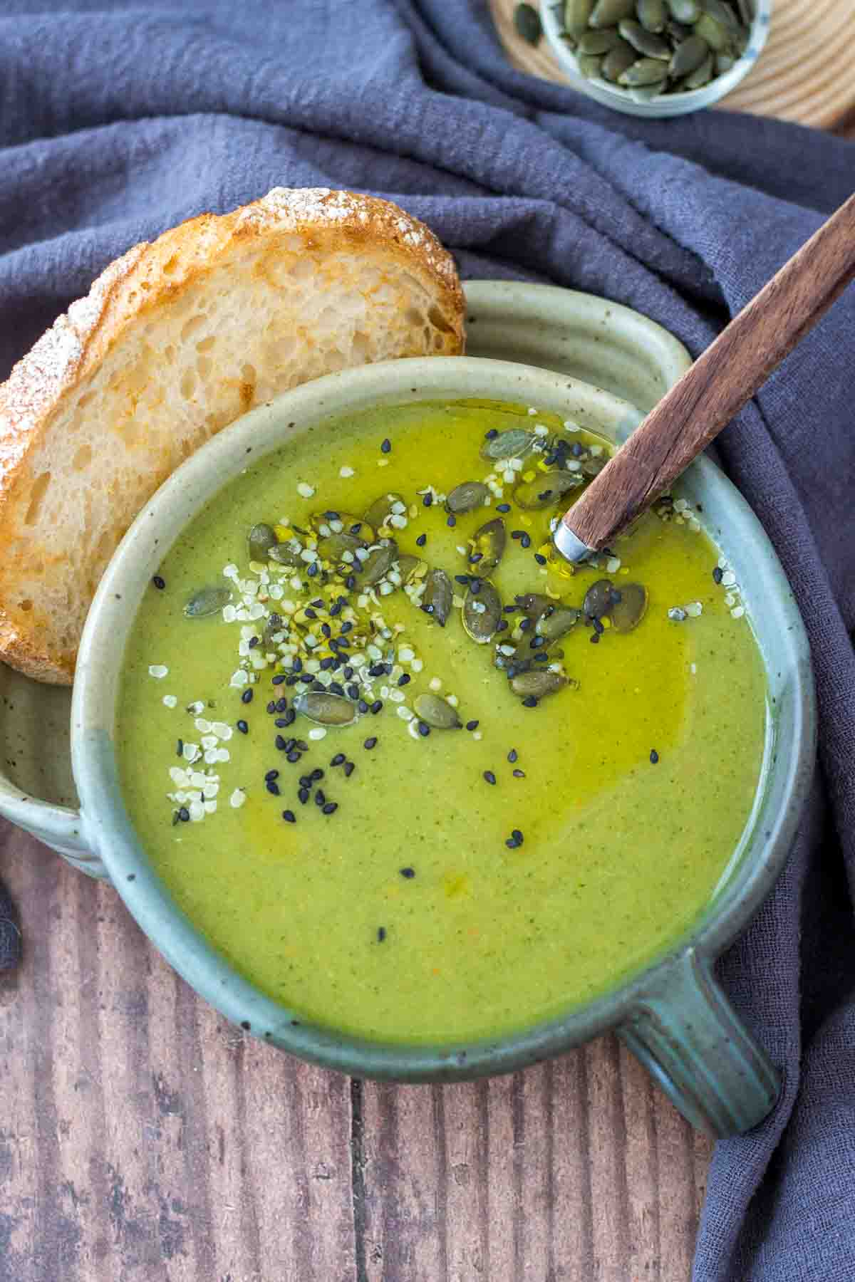 Creamy broccoli soup served in a bowl with a slice of bread, topped with pumpkin seeds.