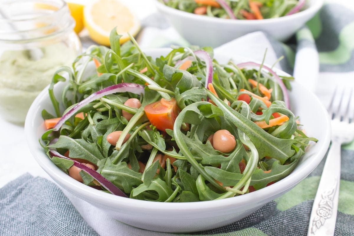 Arugula Beans Salad topped with creamy avocado dressing is a simple yet delicious HEALTHY meal. This very nutritious spring salad is easy to made and can be eaten anytime. CLICK to grab the recipe or PIN for later! natlieshealth.com #vegan #glutenfree #vegetarian #healthy #salad