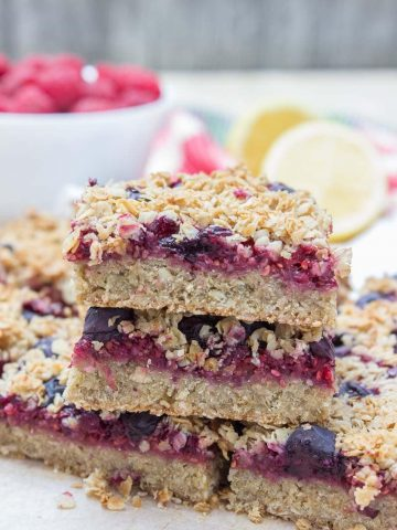 Wholesome Berry Banana Breakfast Oat Bars filled with fresh raspberries and blueberries, made with all HEALTHY ingredients. These bars are vegan, dairy-free, refined sugar-free and gluten-free. Perfect low-calorie summer breakfast that the whole family will devour. #vegan #glutenfree #sugarfree #dairyfree #healthy #oatmeal #oats #family #kidsfriendly #whole30 #weightloss #skinny #lowcalorie #wholegrain   natalieshealth.com