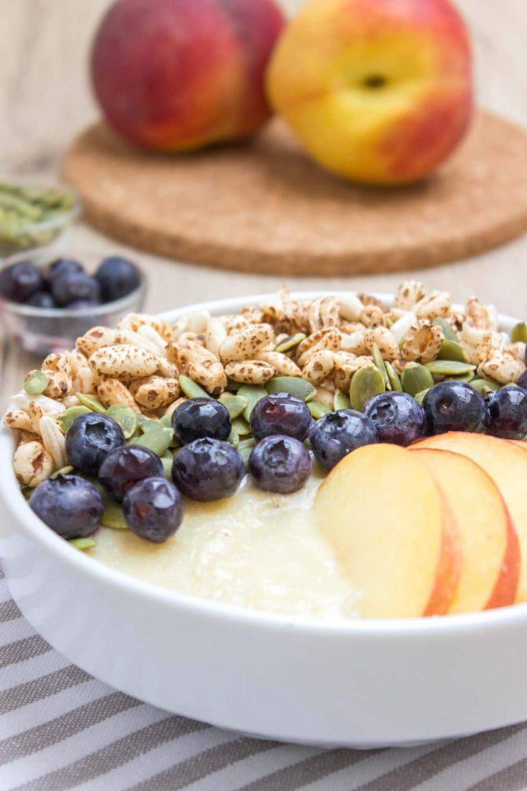 Pineapple Peach Smoothie Bowl with fresh blueberries and pumpkin seeds