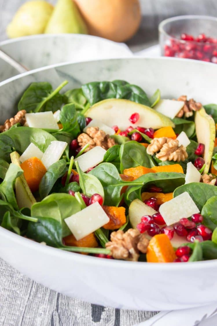 Roast Pumpkin Pear Salad made with spinach, roasted pumpkin, pomegranate, pear, walnuts, and cheese topped with Pumpkin Seed Oil Vinaigrette.