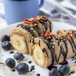 Chocolate Peanut Butter Banana Roll-Ups with crepes peanut butter and bananas drizzled with raw chocolate.