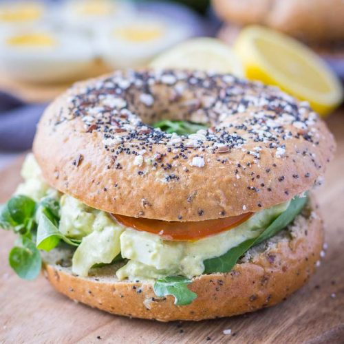 Healthy mayo-free Avocado Egg Salad served with fresh veggies in a whole-grain bagel