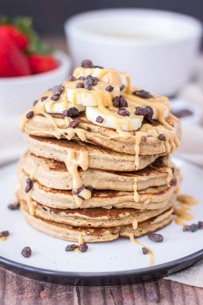 Peanut Butter Oatmeal Pancakes topped with banana, maple peanut butter syrup, and chocolate