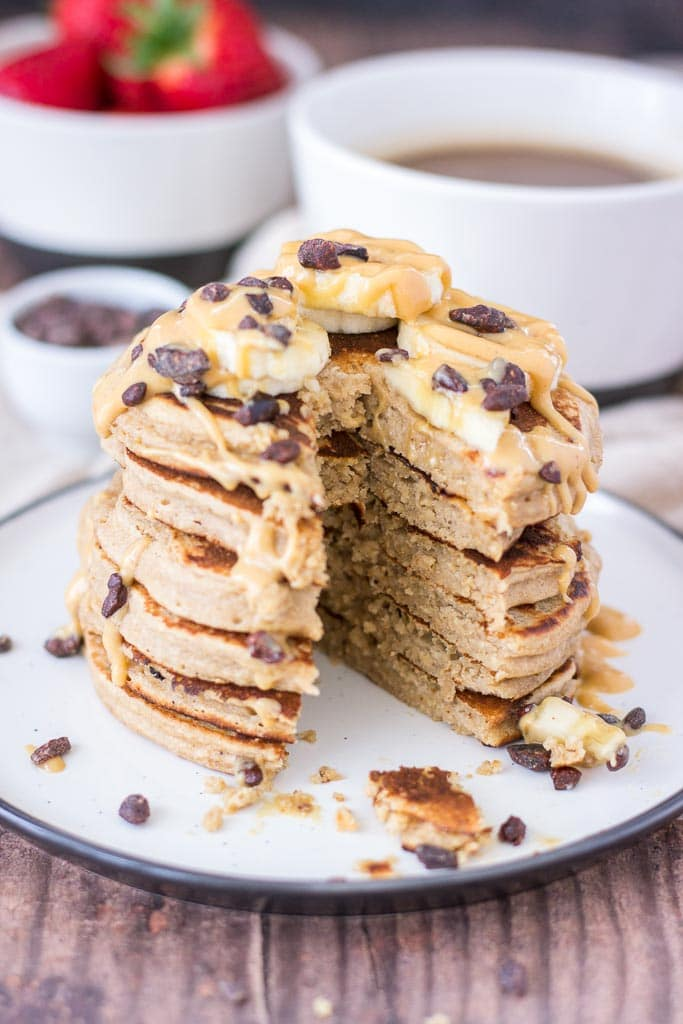 Healthy gluten-free Peanut Butter Pancakes topped with banana and maple peanut butter syrup