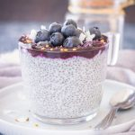 Blueberry Coconut Chia Pudding made with coconut cream topped with blueberry sauce, fresh blueberries, and coconut chips served in a glass bowl.