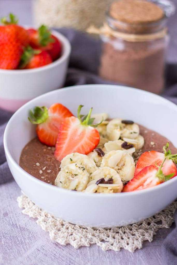 Healthy chocolate oatmeal porridge topped with banana and fresh strawberries
