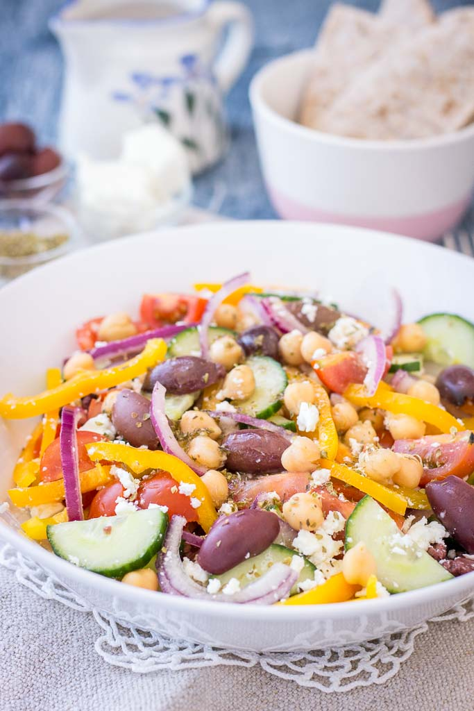 Greek Chickpea Salad with tomatoes, cucumber, olives, feta, and Greek Salad Dressing served in a bowl