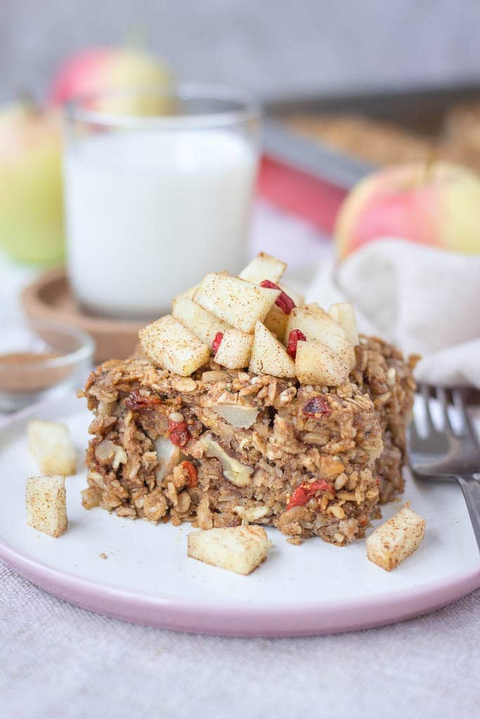 Slice of apple cinnamon baked oatmeal topped with slices of fresh apples served on a plate