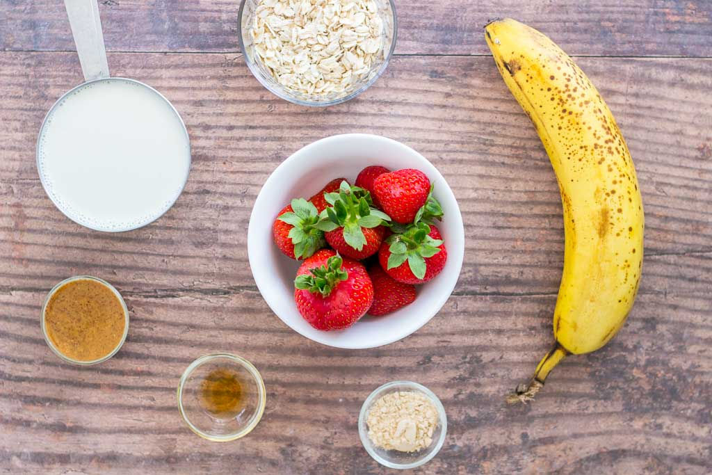 Ingredients for making strawberry oatmeal smoothie, strawberries, banana, oats, almond butter and milk