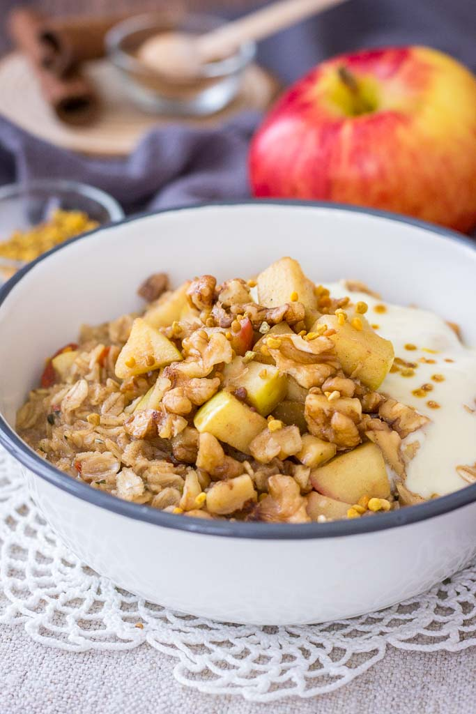 Apple Cinnamon Oatmeal served in a bowl, topped with caramelized apples and walnuts, and yogurt