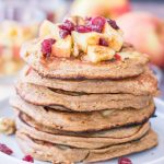 Stacked Apple Oatmeal Pancakes topped with diced apple, walnuts, and dried cranberries served on a plate
