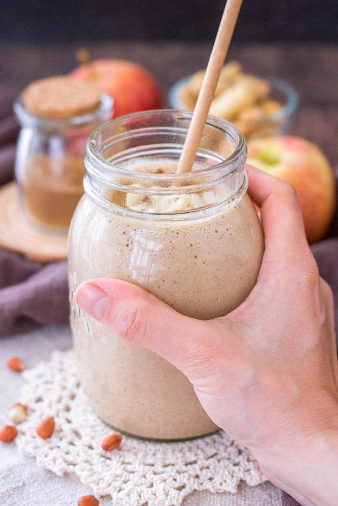 Hand holding a Apple Peanut Butter Smoothie served with a straw in a glass jar topped with creamy peanut butter and crushed peanuts