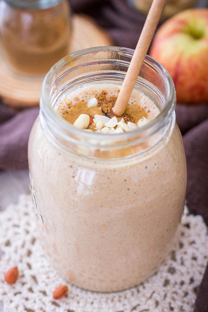 Apple Peanut Butter Smoothie served with a straw in a glass jar topped with creamy peanut butter and crushed peanuts