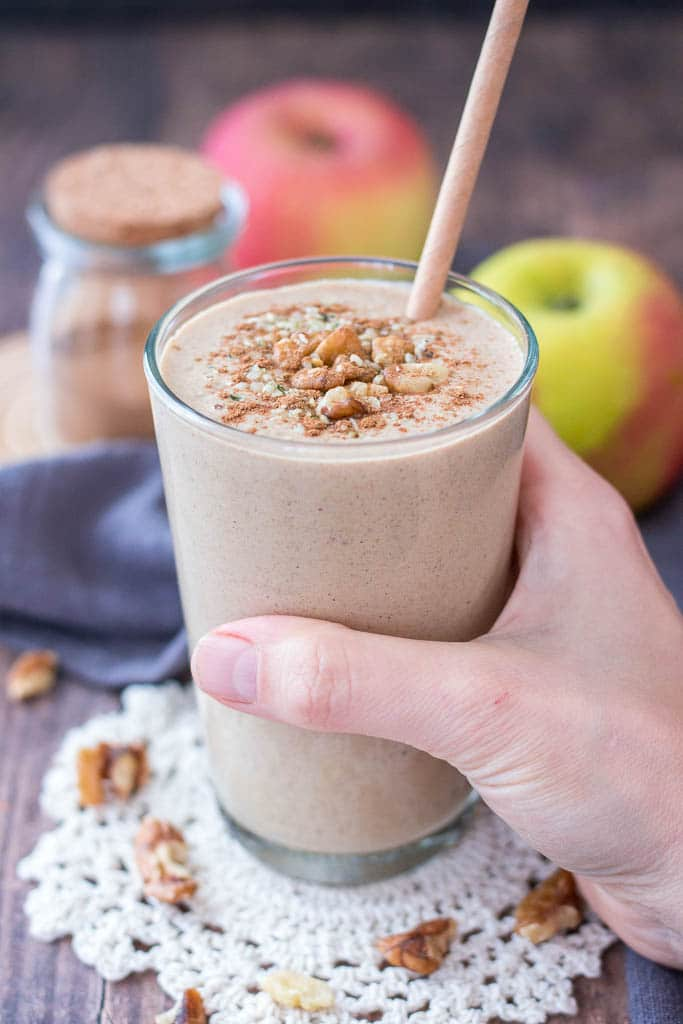 Apple Pie Smoothie topped with walnuts cinnamon and hemp seeds served in a glass with a straw