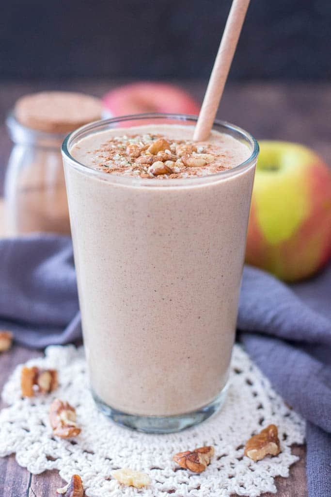 Healthy Apple Pie Smoothie topped with walnuts cinnamon and hemp seeds served in a glass with a straw