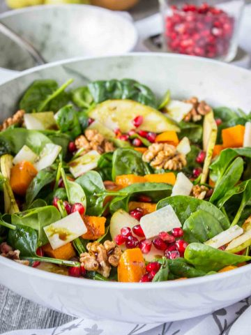 Pumpkin Pear Salad with baby spinach and walnuts topped with cheese and seeds served in a bowl