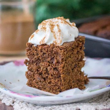 A slice of Gingerbread Cake topped with whipped cream served on a plate