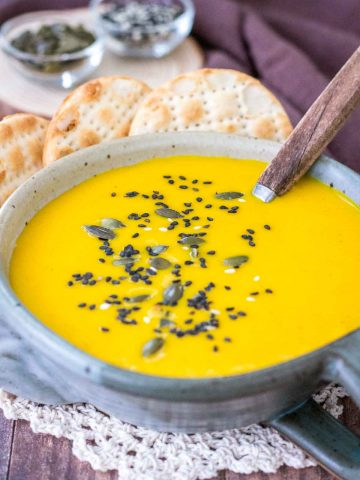Creamy Carrot Curry Soup served in a bowl with crackers topped with seeds