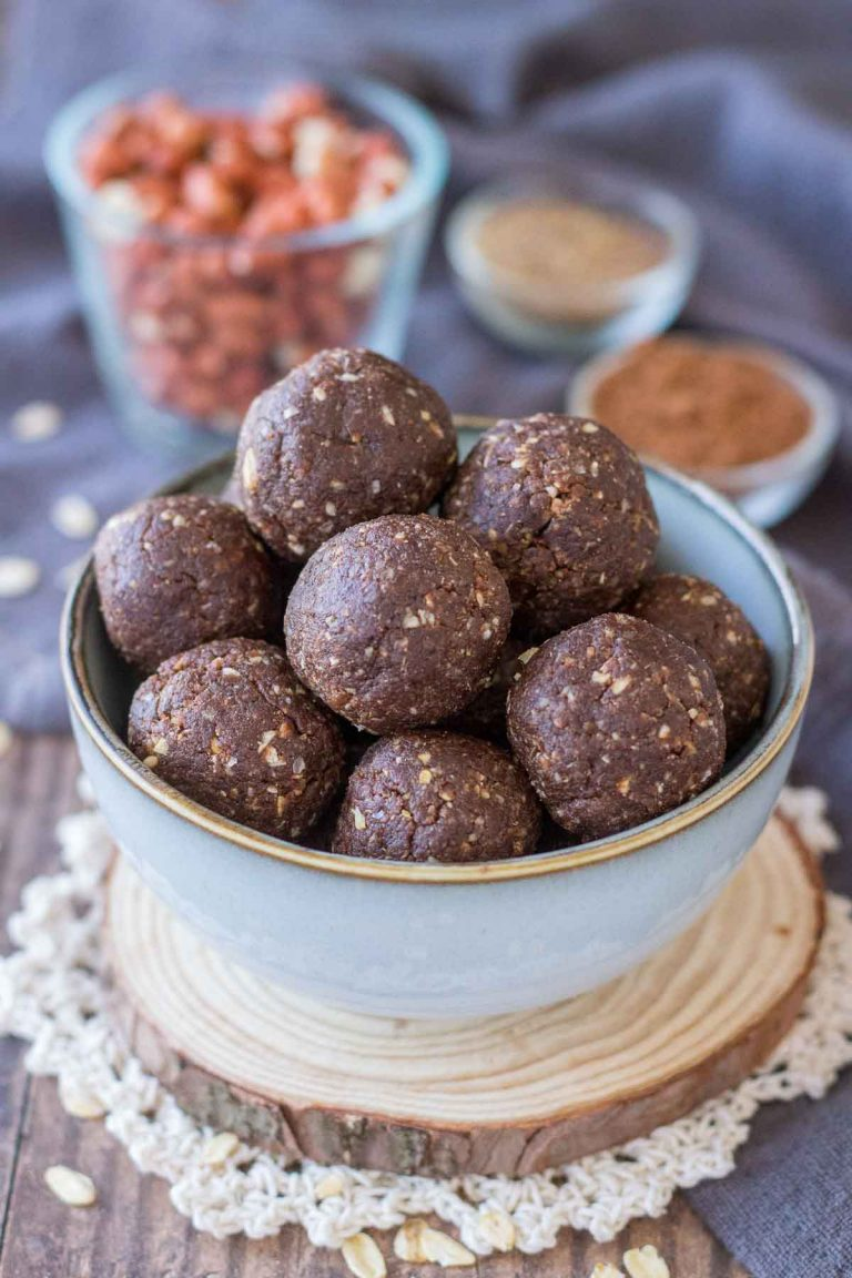 Chocolate protein balls served in a small bowl, spices and raw peanuts in a background