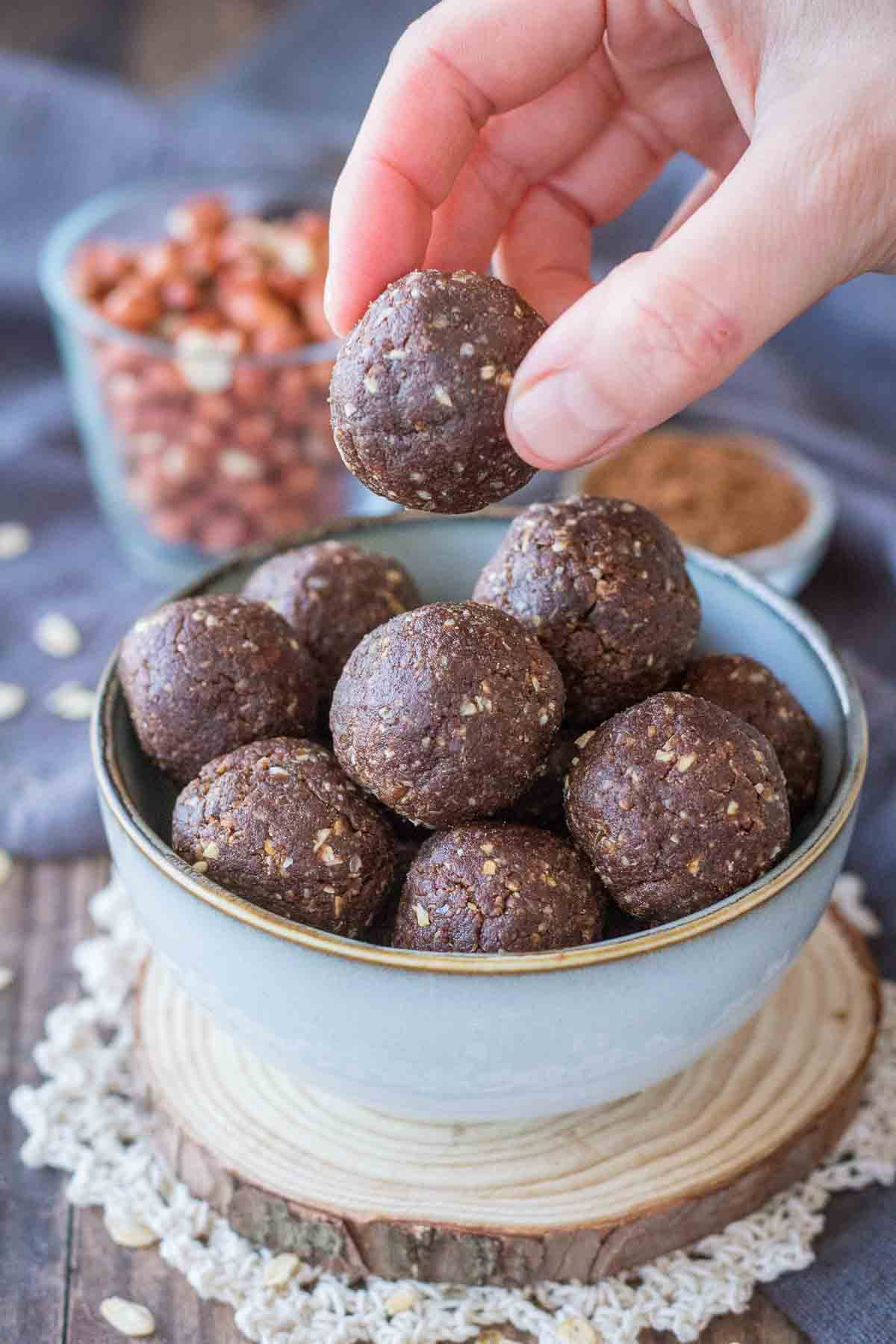 Hand taking Chocolate Peanut Butter Balls from a bowl