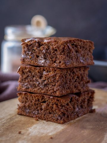 Almond butter brownies sliced and served on a wooden plate