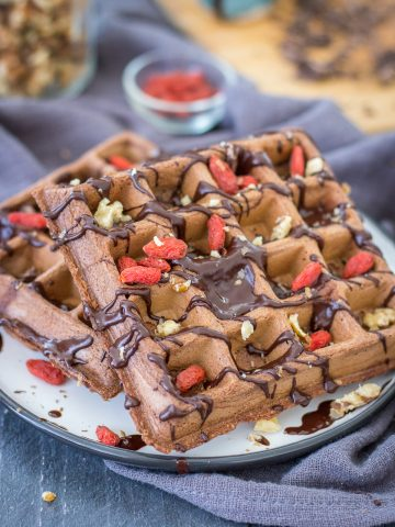 Chocolate waffles served on a plate drizzled with melted chocolate