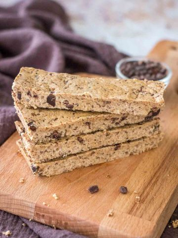 Four Cookie Dough Protein Bars stacked on a wooden plate