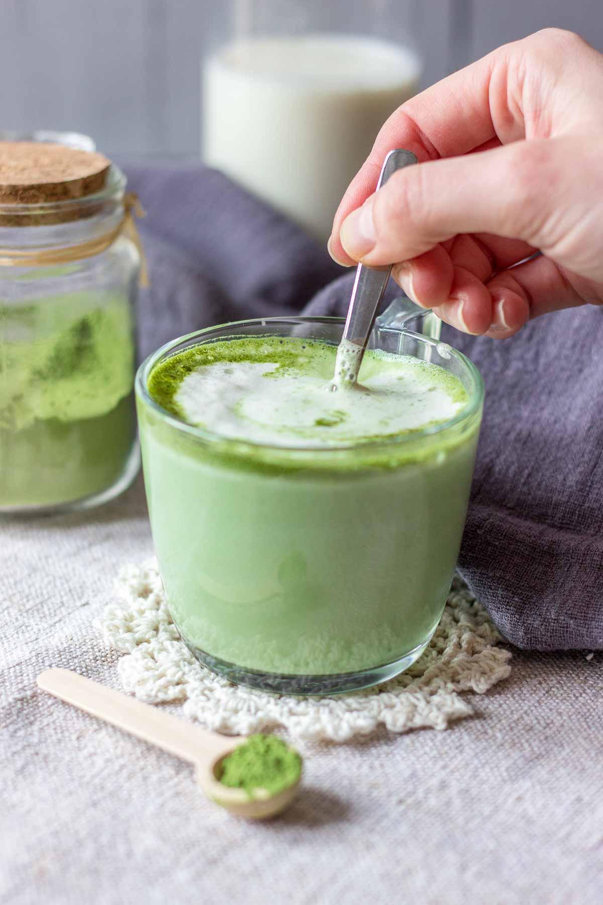 Hand mixing a matcha green tea latte served in a mug