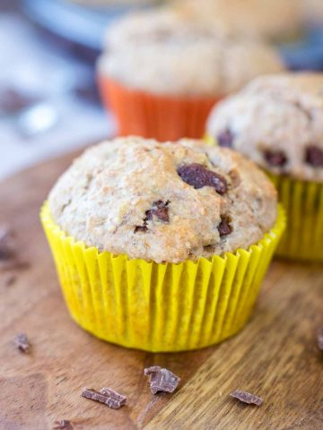 Banana chocolate chip muffins served on a wooden plate.