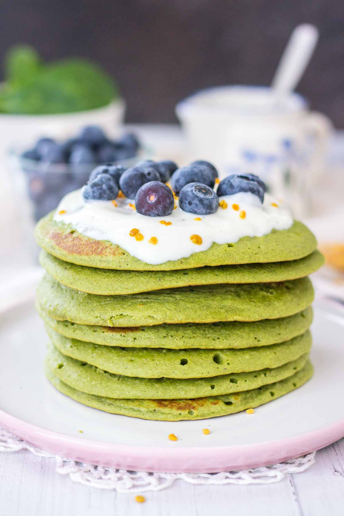Healthy Matcha Pancakes topped with yogurt and blueberries.