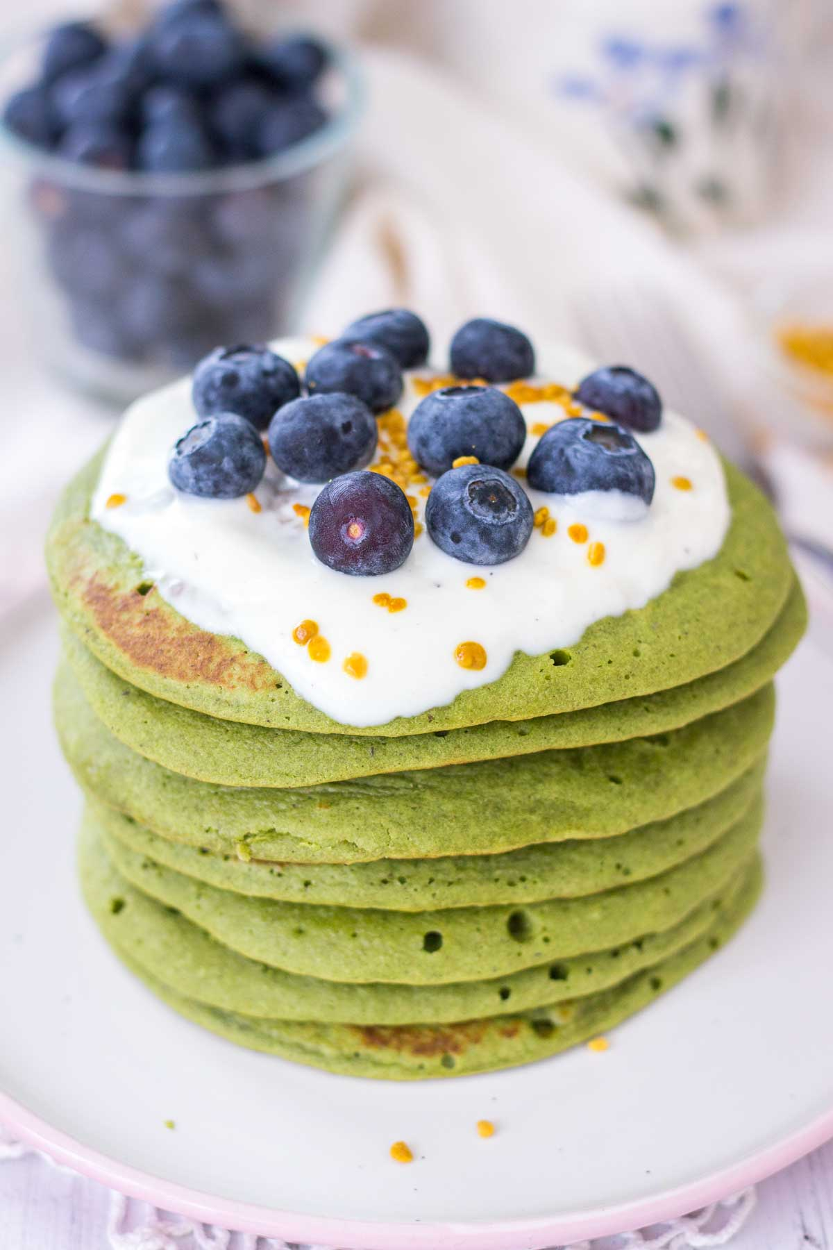 Matcha green tea pancakes served on a plate topped with fruits.