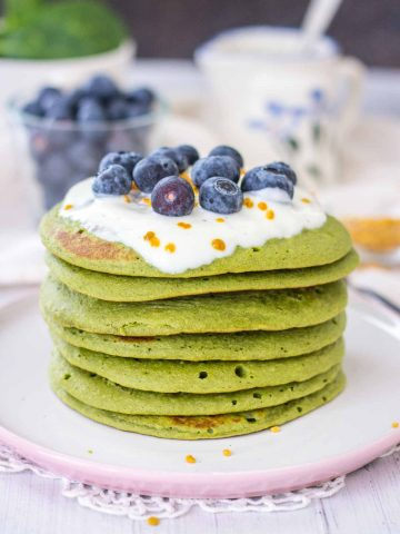 Matcha Pancakes topped with yogurt and blueberries served on a plate.