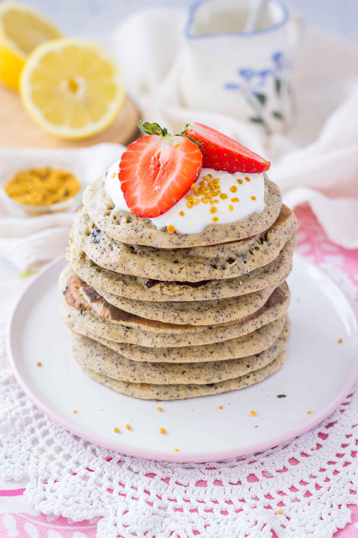 Healthy lemon pancakes made with poppy seeds served on a plate with fresh strawberries.