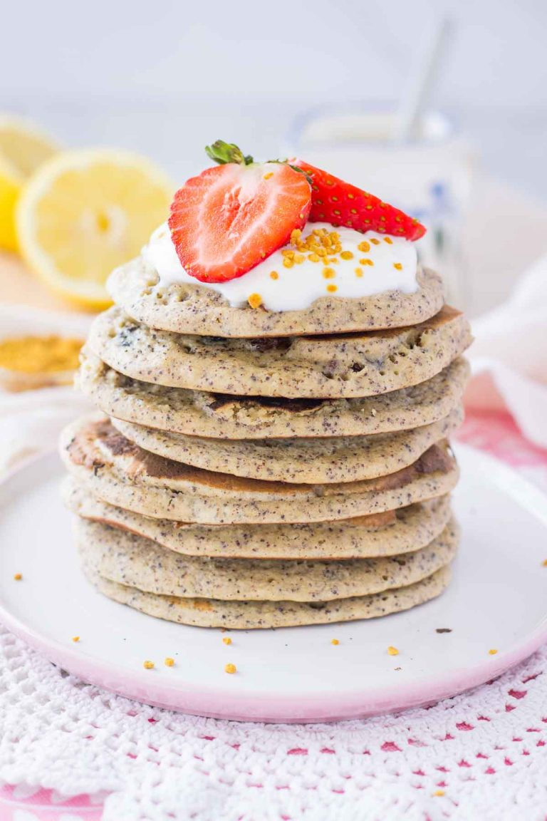 Lemon Poppy Seed Pancakes served on a plate topped with yogurt and strawberries.