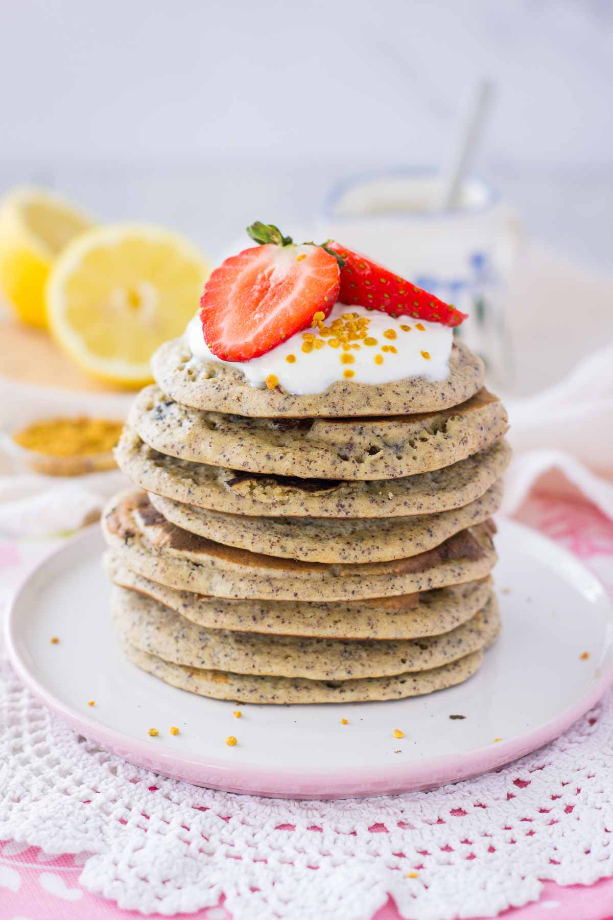 Lemon poppyseed pancakes served on a plate topped with yogurt and strawberries.