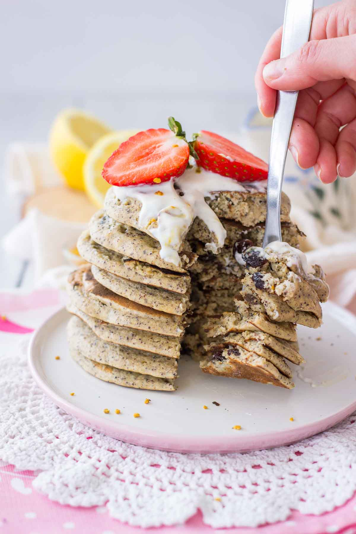 Lemon pancakes made with oats and poppy seeds served on a plate with fresh strawberries.