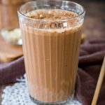 Coffee Smoothie served in a smoothie glass topped with cacao, oats and chocolate