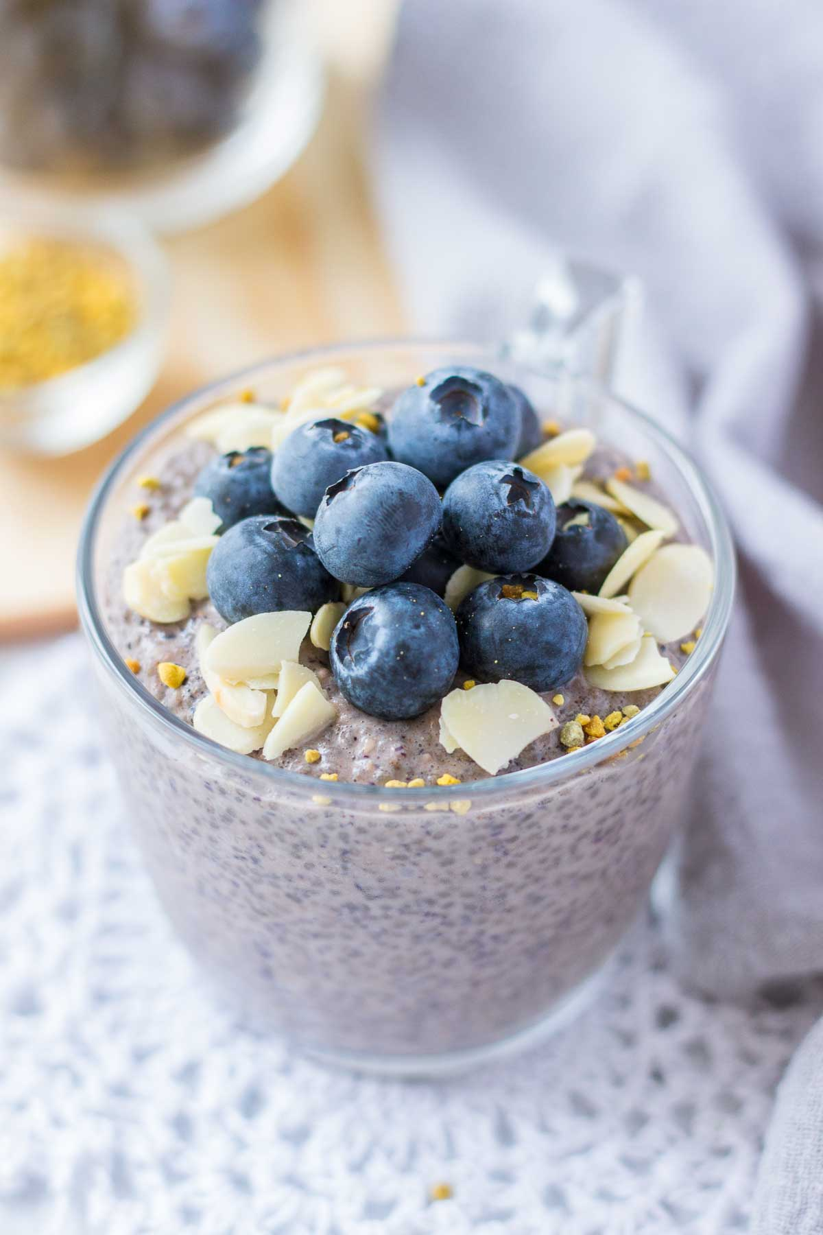 Close up of Blueberry Chia Pudding served in a glass bowl topped with fresh blueberries and almonds