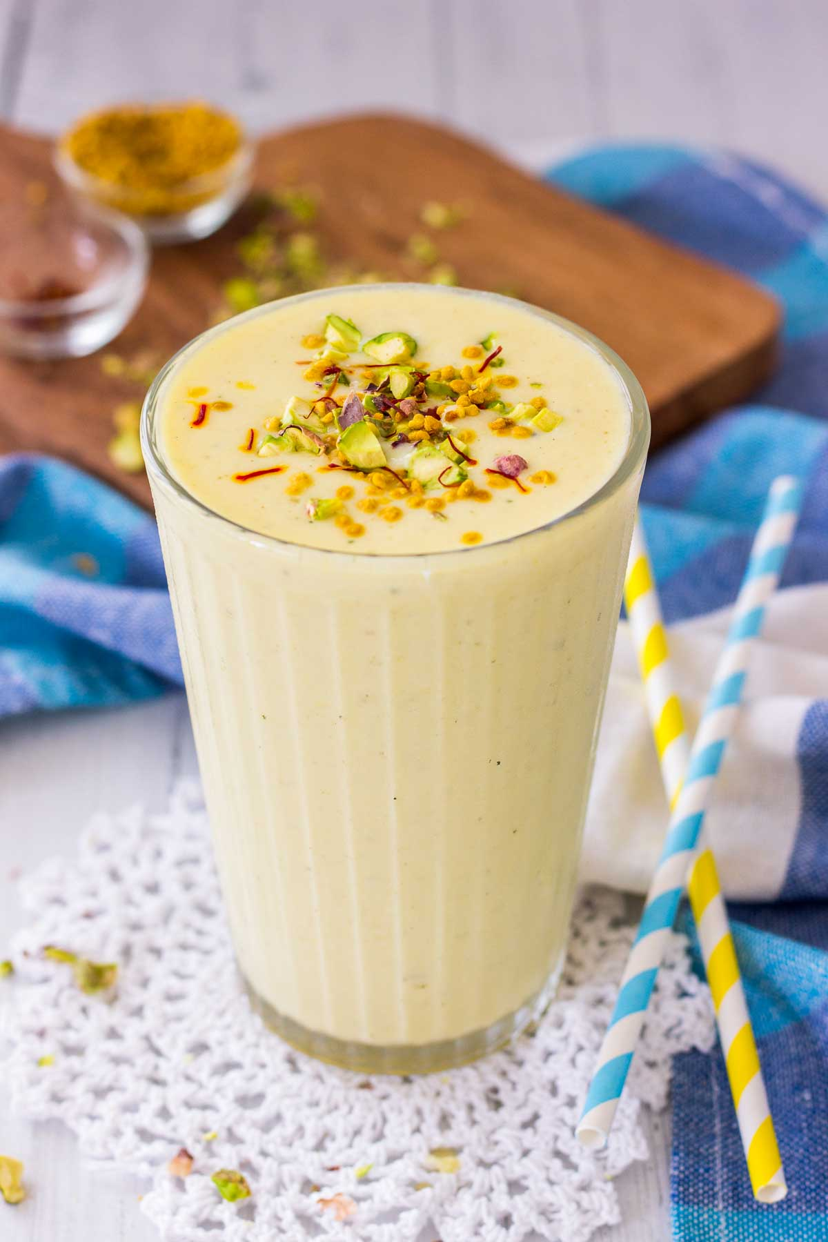 Mango Lassi served in a glass topped with crushed pistachio