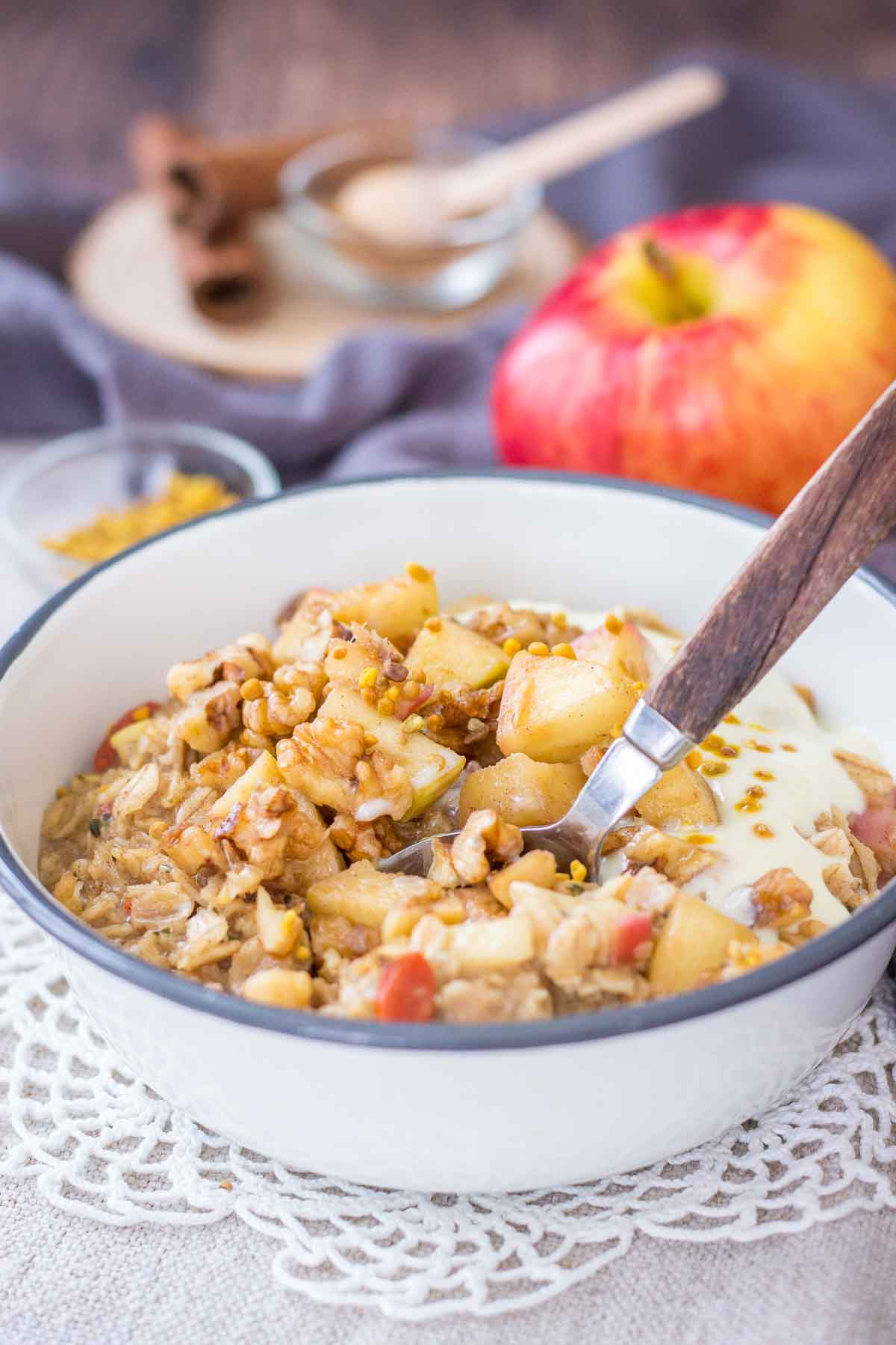 Apple Cinnamon Oatmeal served in a bowl topped with diced apples, walnuts and yogurt