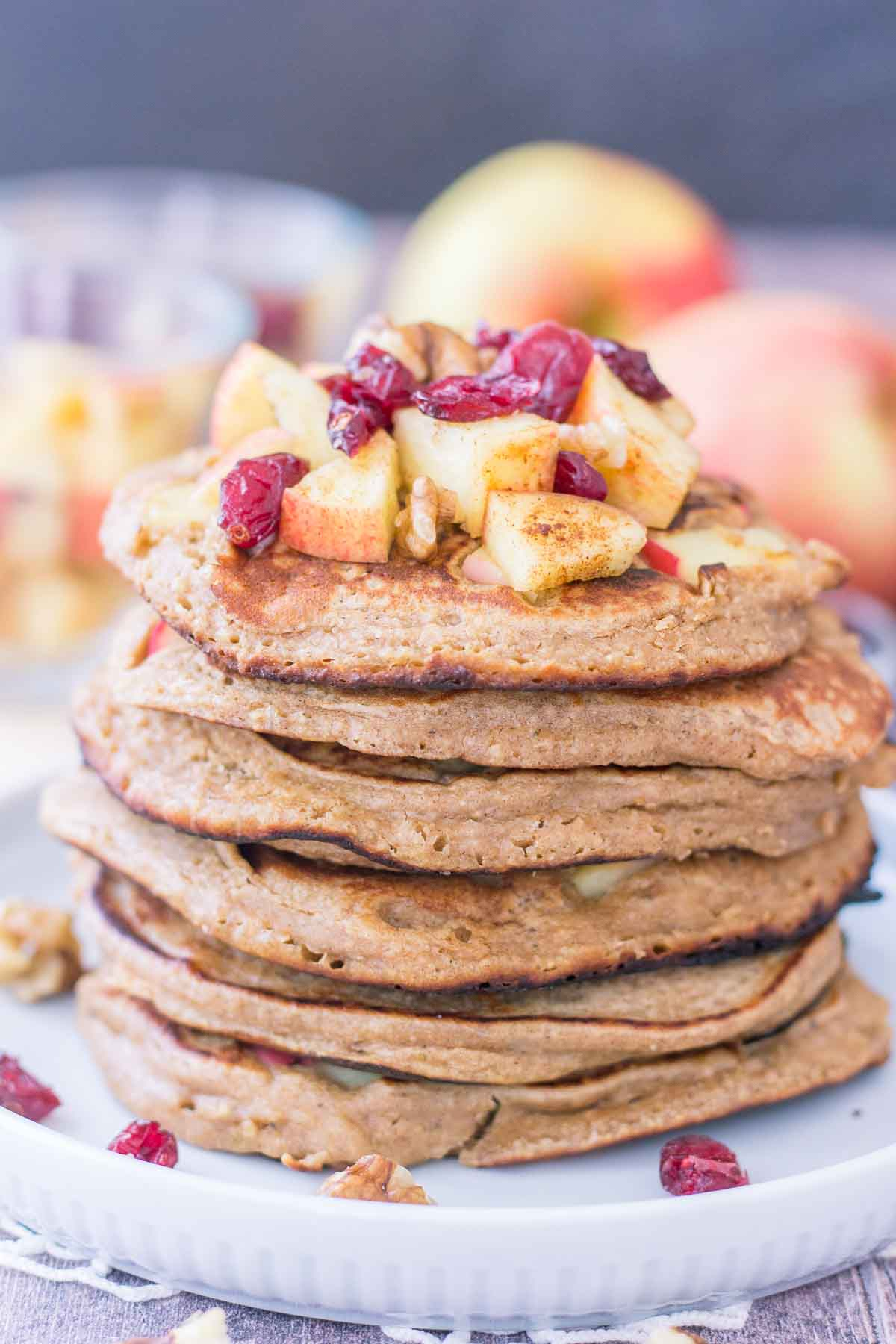 Apple Oatmeal Pancakes stacked on a plate topped with diced apples and cranberries