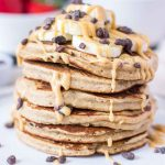 Peanut Butter Oatmeal Pancakes stacked on a plate topped with slices of banana and chocolate