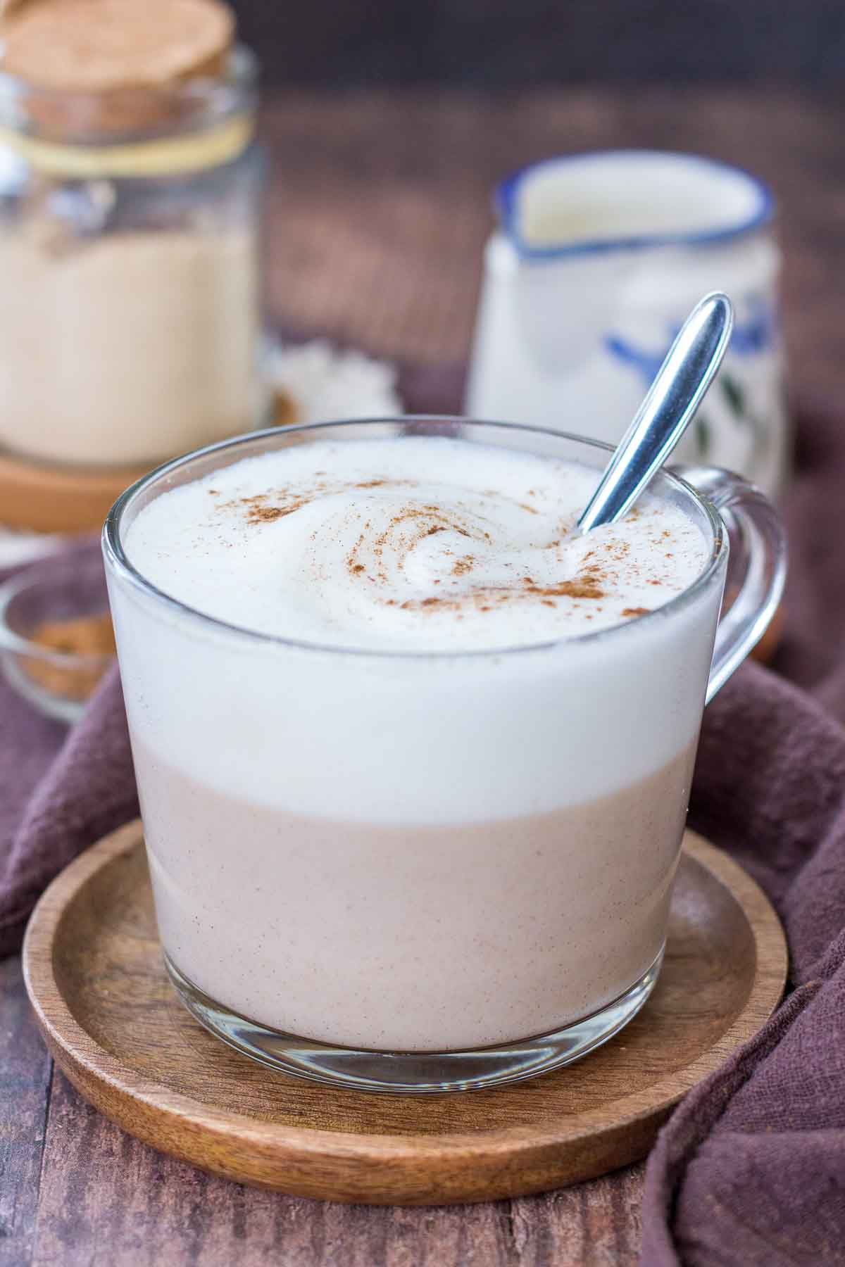 Maca Latte served in a clear mug topped with milk foam and cinnamon